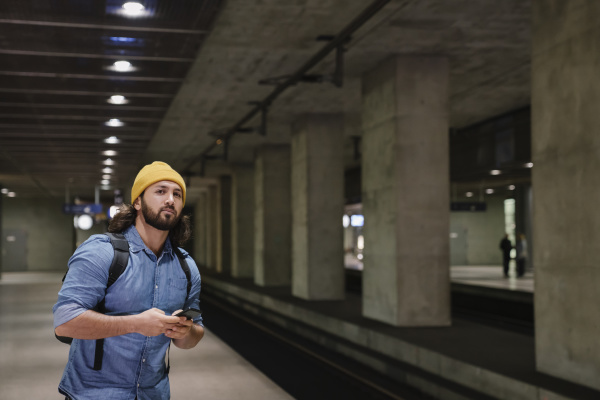 portrait of man with smartphone waiting
