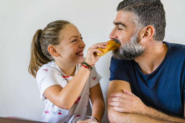 happy daughter feeding father at home