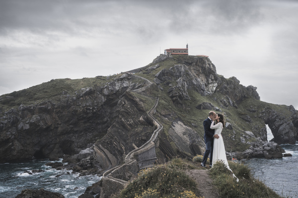 bridal couple on bridge gaztelugatxe spain