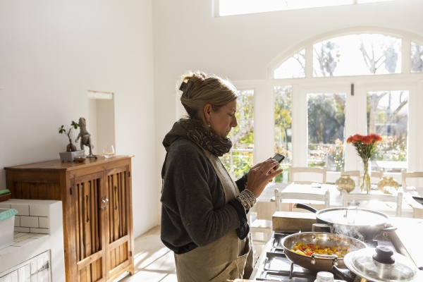 adult woman in kitchen reading text