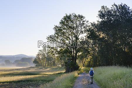 full length of senior woman hiking